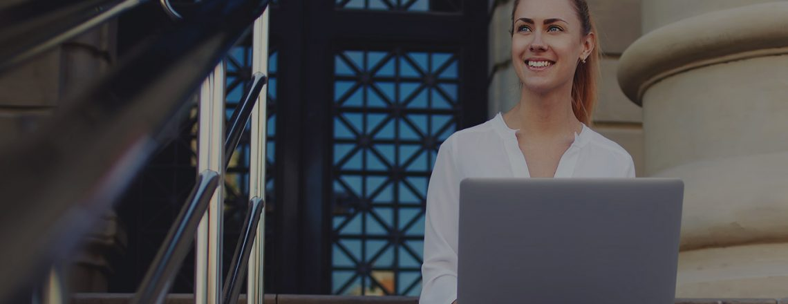 woman smiling sitting outside on laptop